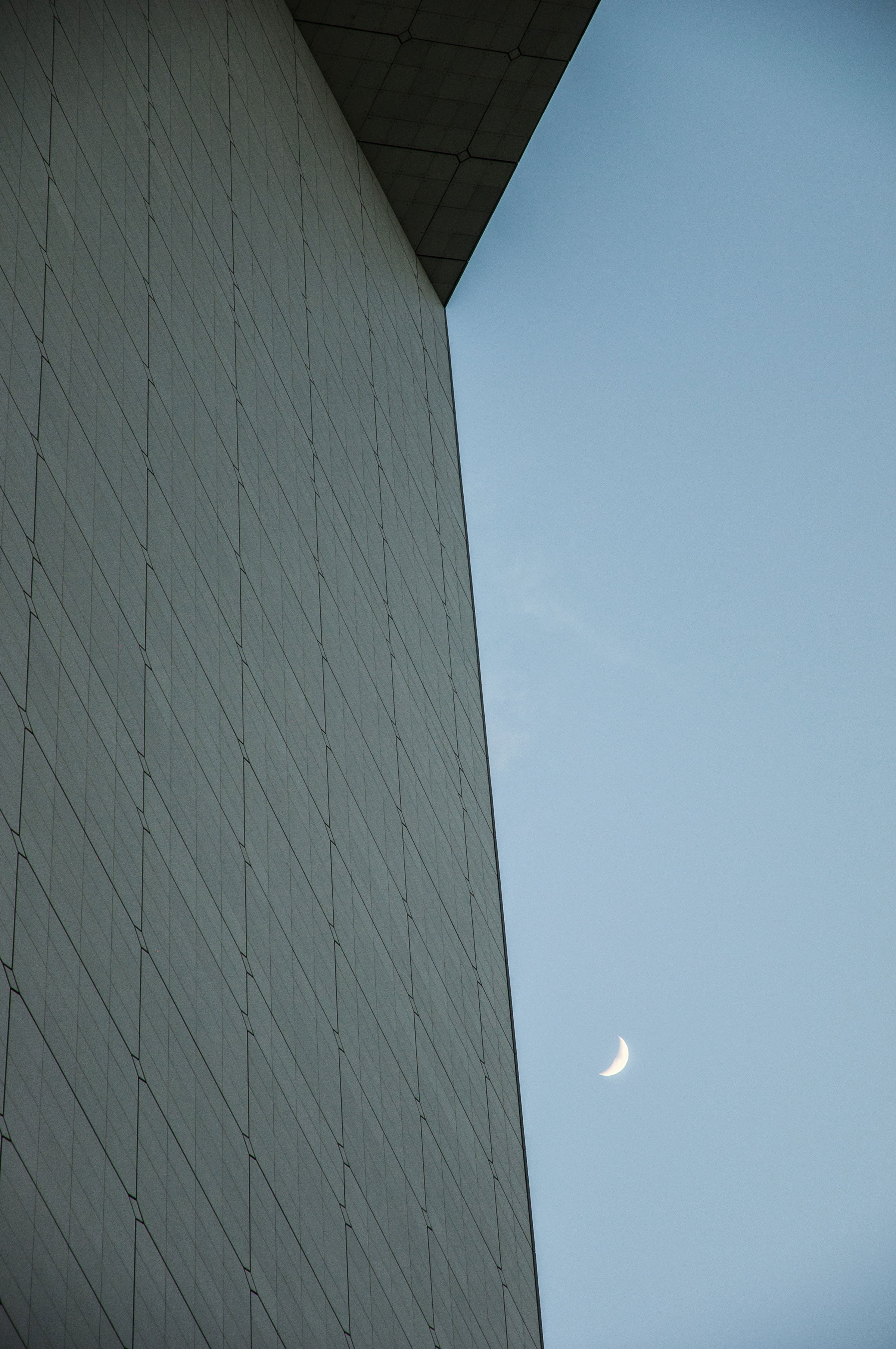 Abstract architecture photography with the moon and the top of the Arch of La Défense, Paris, France. (Nos Dren)