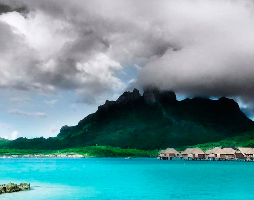 French Polynesia, Bora Bora island, mount Otemanu under clouds with high constrat, behind the blue lagoon and the stilt houses. (Nos Dren)