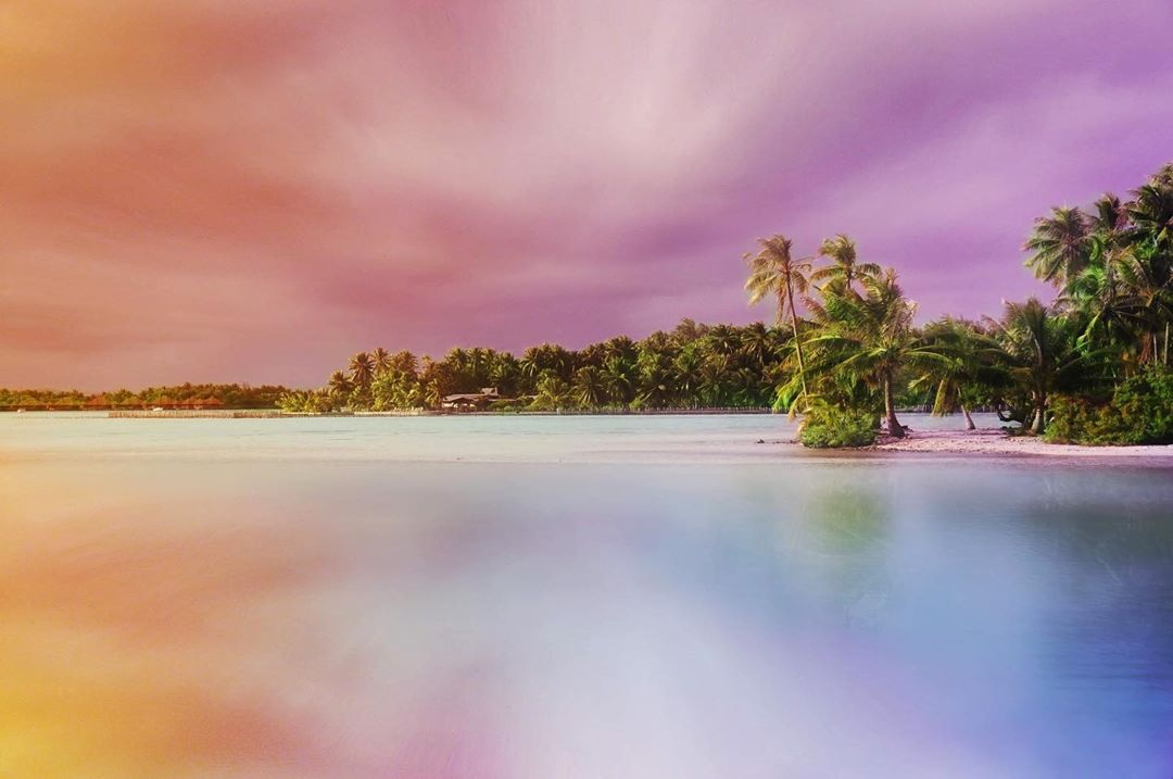 French Polynesia, Bora Bora island, amazing colorful sky and reflection on the blue lagoon took from the atoll with many palm trees and coco trees. (Nos Dren)