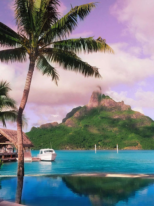 French Polynesia, Bora Bora island, view from the pool in Le Meridien Bora Hotel harbor with Mount Otemanu in the background, palm tree and boat ahead. (Nos Dren)