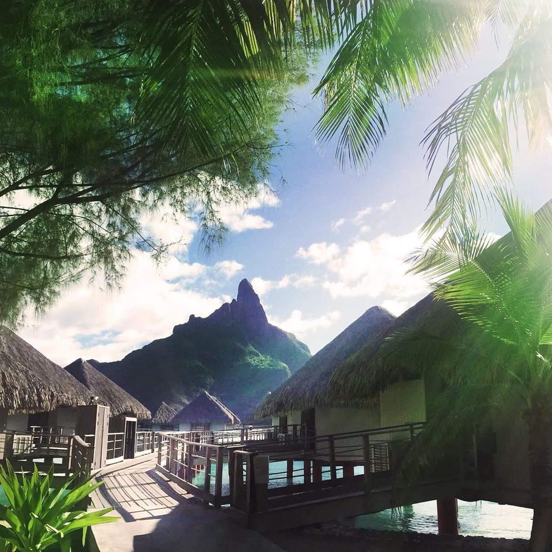 French Polynesia, Bora Bora island, Mount Otemanu view from the stilt houses and palm trees from Le Meridien Bora Hotel. (Nos Dren)