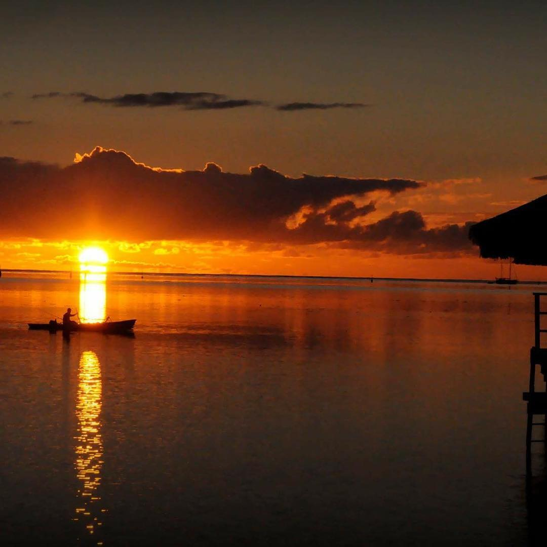 French Polynesia, Moorea or Mo'orea island, fisherman returning to harbor by sunrise with a nice contrast. (Nos Dren)