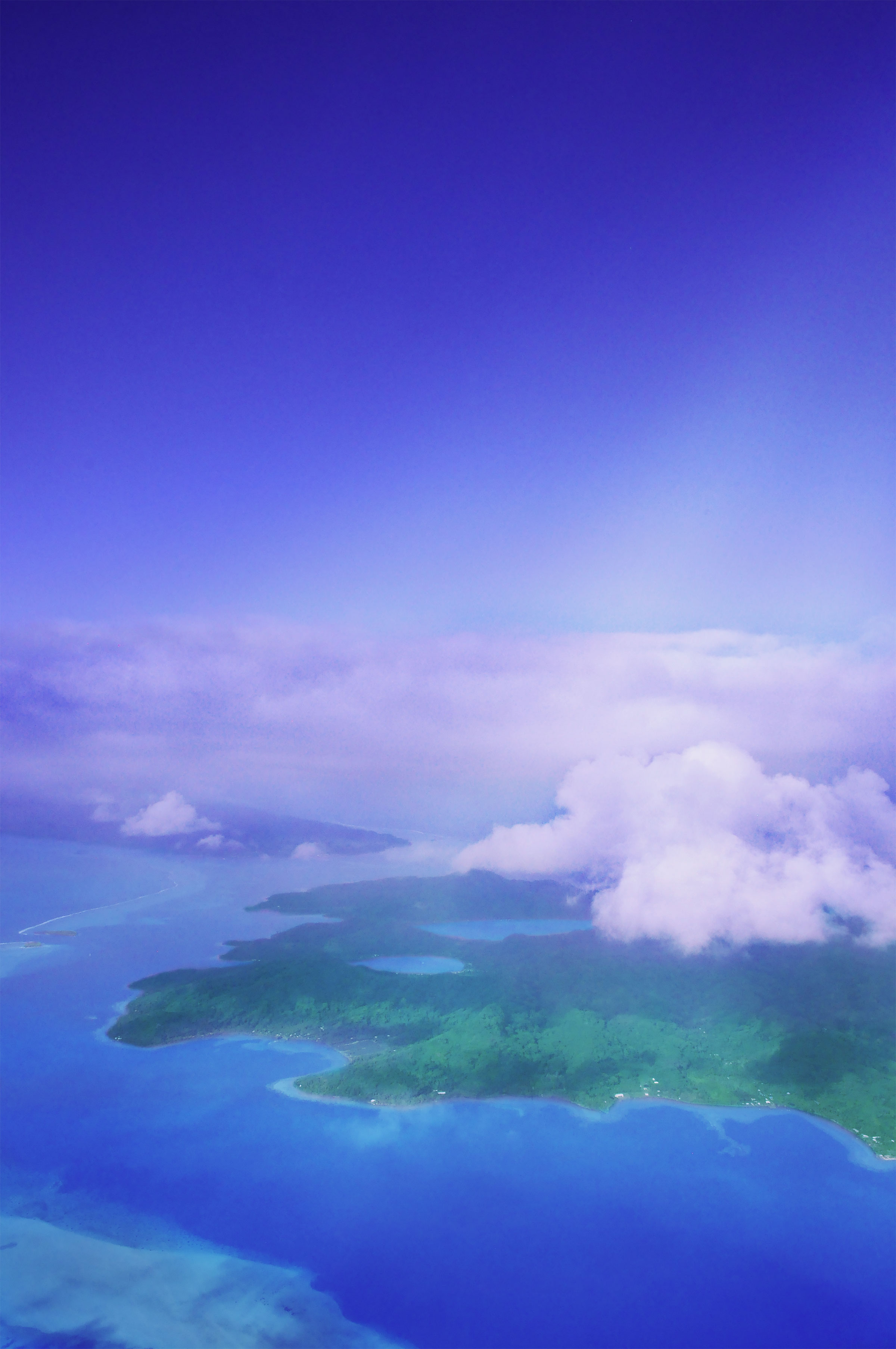 French Polynesia, Raiatea island and its blue bays Faaha and Haamene view from the sky, and the island of Tahaa just behind. (Nos Dren)